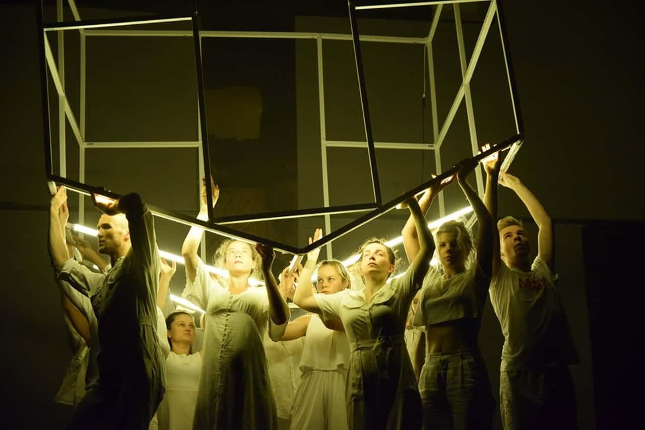 Scena spektaklu. Tłum młodych osób w białych strojach trzyma się rusztowania, które układa się w kształt domu. Na rusztowaniu przymocowane są świetlówki, które palą się na żółty kolor.