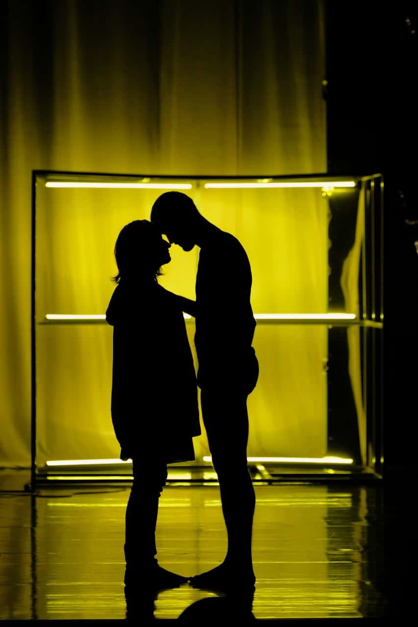 Scena spektaklu. Na tle rusztowania widać w cieniu dwie sylwetki: chłopaka i dziewczyny. Przytulają siędo siebie.