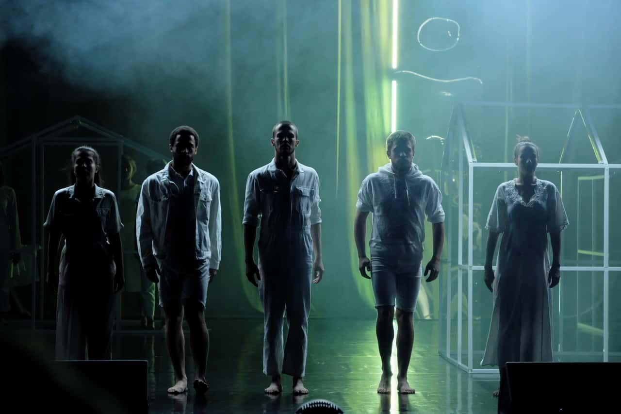 Scena spektaklu. Pięc postaci stoi obok siebie, twarzą do wdowni. Ich sylwetki są w cieniu. W tle rusztowanie w kształcie domku. Postaci ubrane są w białe kostiumy.