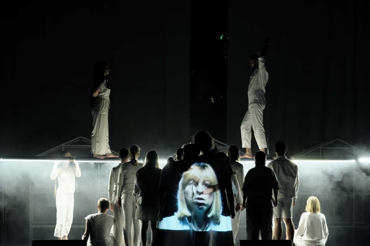 Scena spektaklu. Tłum postaci w białych strojach stoi na rusztowaniu na różnych wysokościach. Na plecach jednej zpostaci, która stoi plecami do widowni, wyświtlania jest twarz młodej dziewczyny.