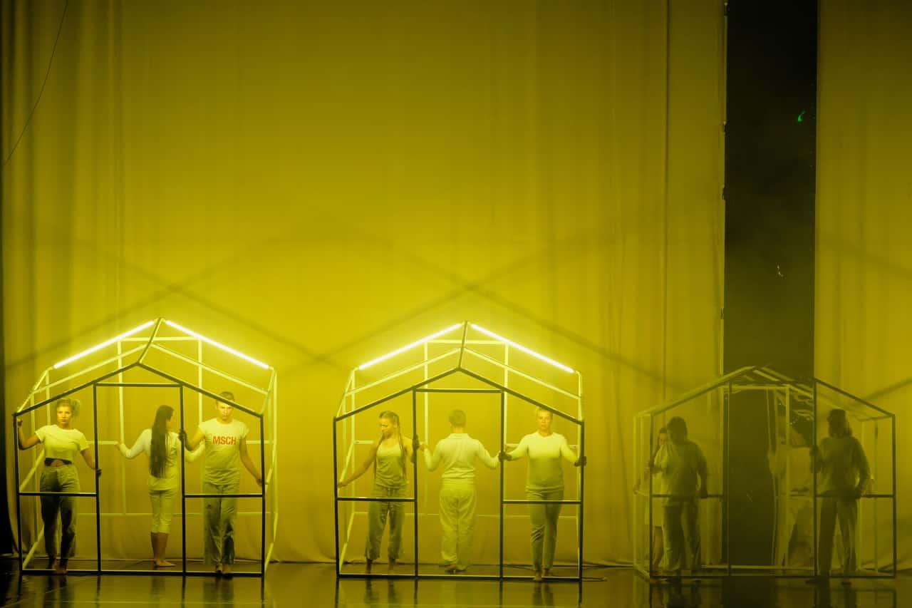 Scena spektaklu. Scena zbiorowa, Trzy grupy osób stoją w trzech rusztowaniach w kształcie domków. Wszyscy ubrani są na biało. Dominuje żółte światło.