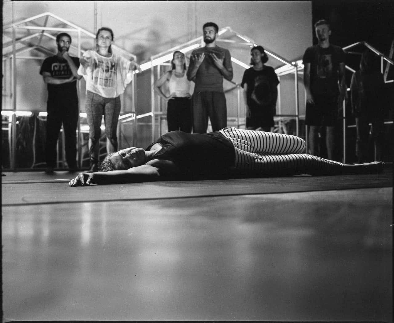 Scena ze spektaklu. Zdjęcie czarno-białe. Na scenie leżu postać, dziewczyna. Nad nią stoi grupa młodych osób. Część patrzy na leżącą dziewczynę, część nie. W tle rusztowania w kształcie domków.
