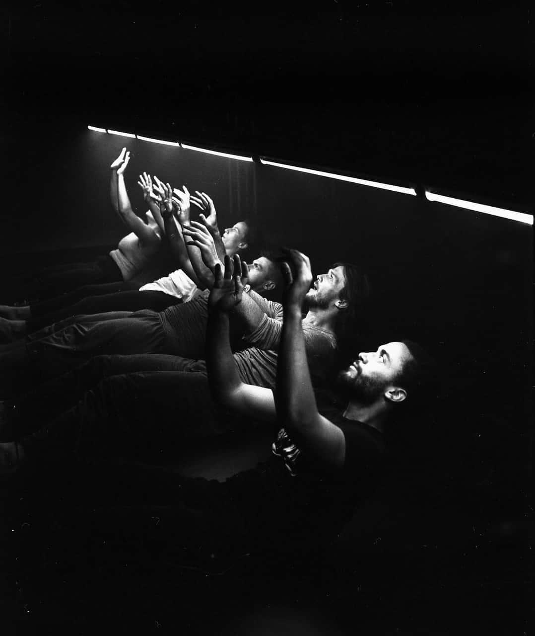 Scena spektaklu. Zdjęcie czarno-białe. Grupa młodych osób lezy koło siebie na podłodze. Wszyscy patrzą w górę. Nad ich głowami co kilkadziesiąt centymetrów widać zapalone świetlówki.