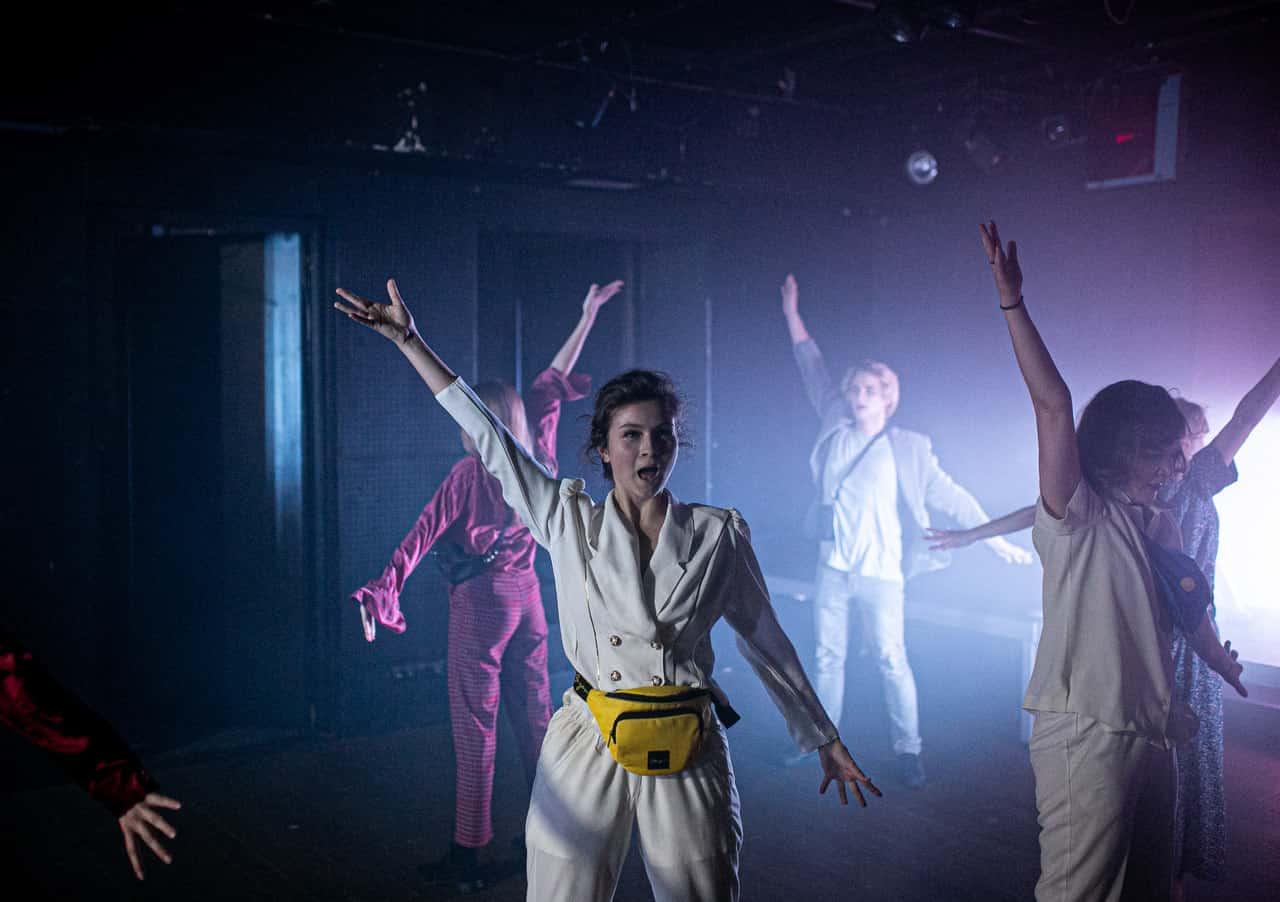 Scena spektaklu. Pięcioro młodych ludzi chodzi w kółko zrękoma wyciągniętymi do góry. Spowija ich kolorowe światło zdominującym odcieniem fioletu.