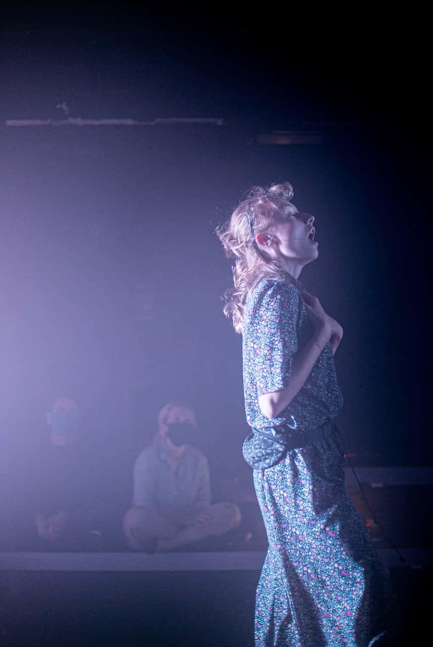 Scena spektaklu. Młoda dziewczyna w sukience w drobny wzór stoi bokiem do publiczności. Ręce ma skrzyżowane na piersiach, twarz skierowaną ku górze. Otwarte usta sugerują, że coś mówi.
