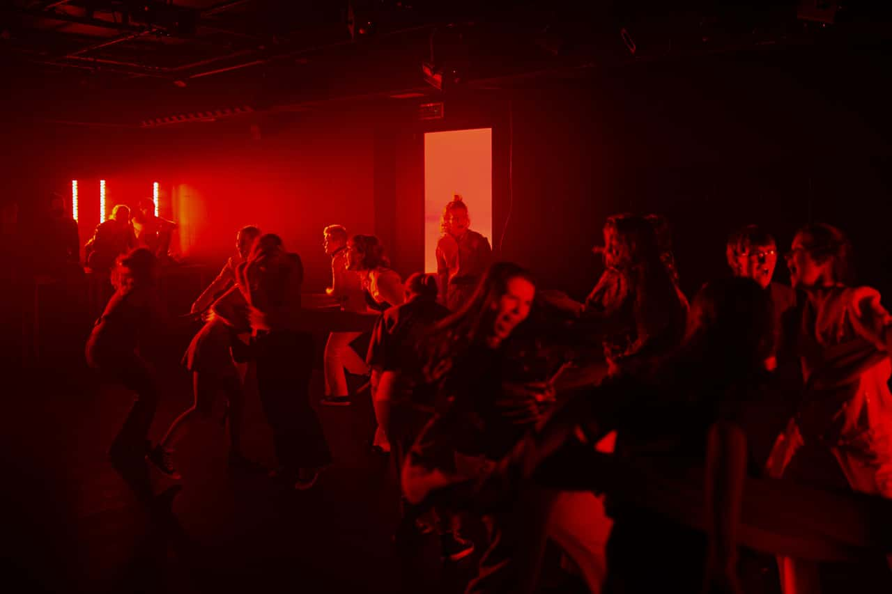 Scena spektaklu. Tłum młodych ludzi w półzgięciu biega po scenie. Spowija ich wyraziste czerwone światło.
