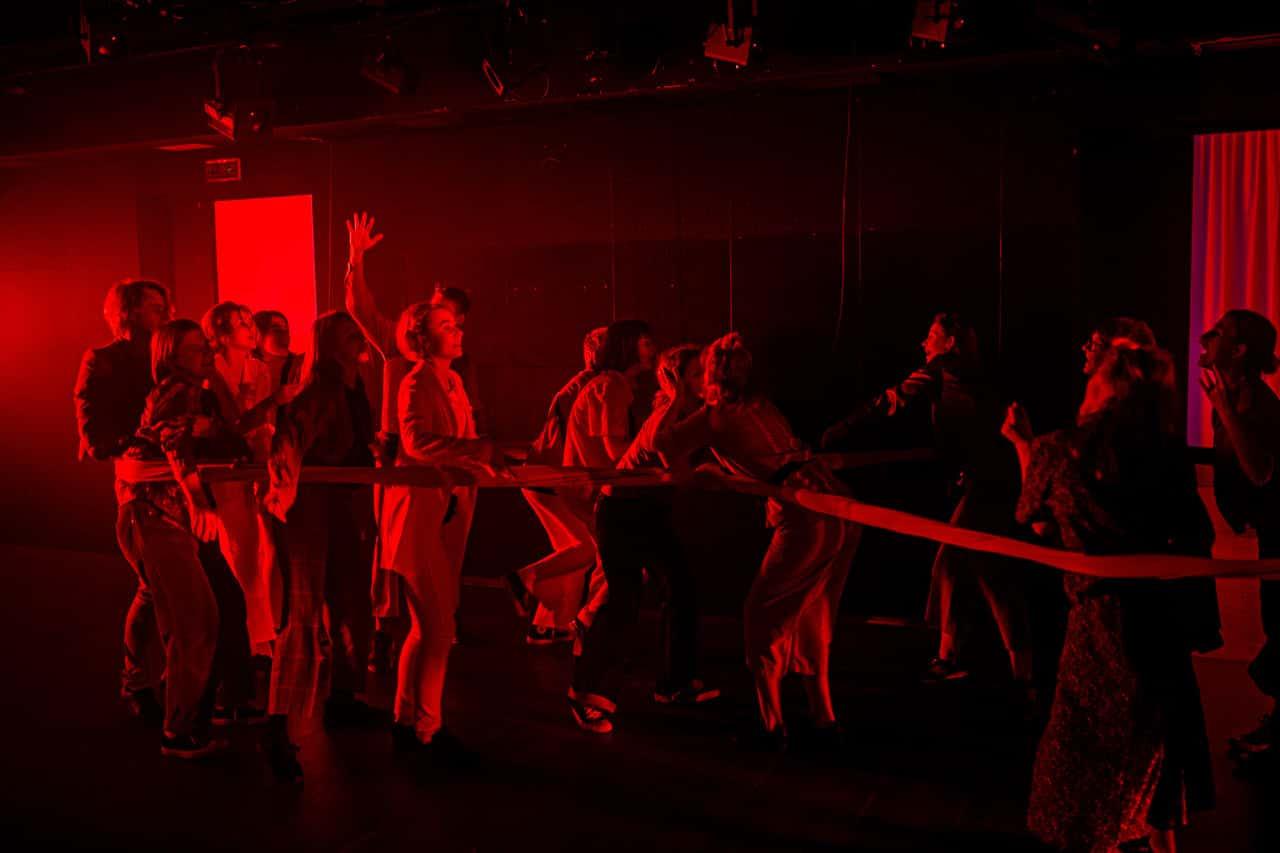 Scena spektaklu. Tłum młodych ludzi biega po scenie. Wszyscy spętani są długim materiałem wdzłuż pasa, który zbija ich w jedną gromadę. Całość sceny spowija mocne czerwone światło.