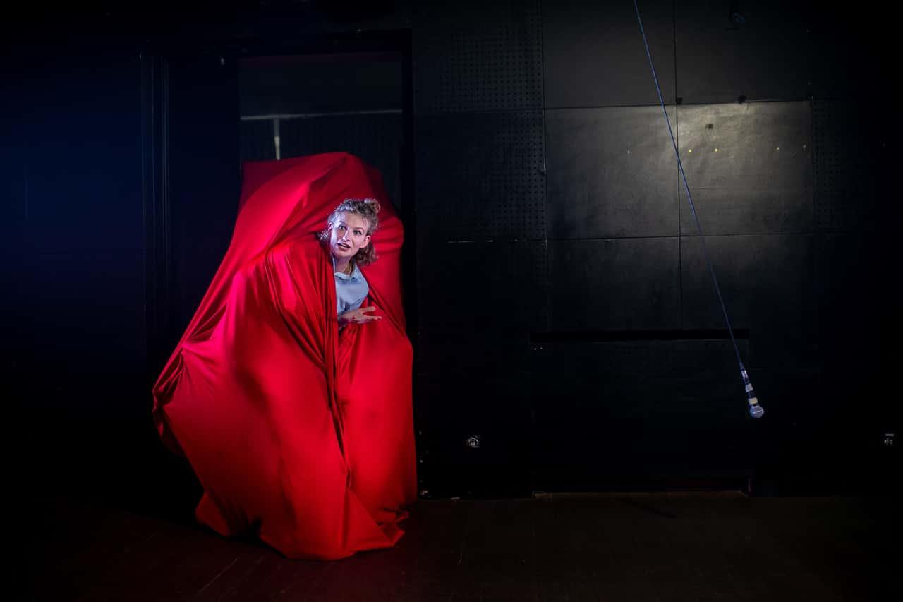 Scena spektaklu. Młoda dziewczyna o krótkich blond włosach schowana prawie cała w czerwonej wielkiej chuście.