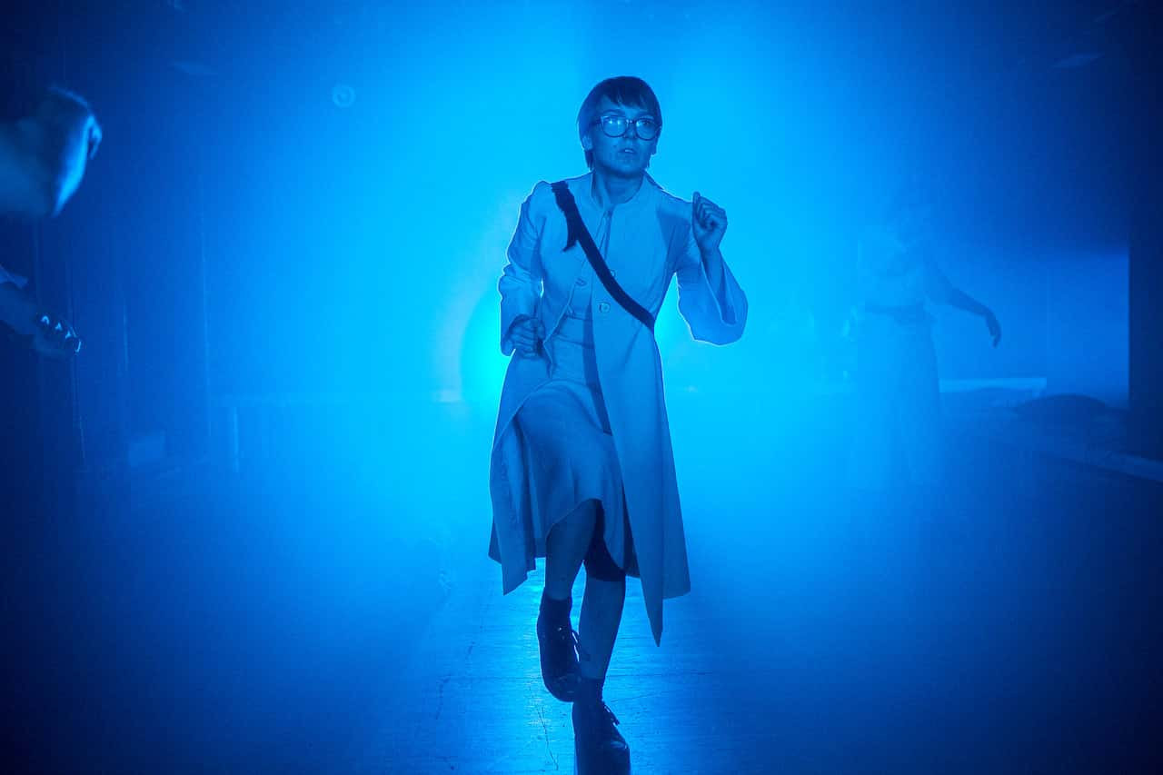 Scena spektaklu. W niebieskim świetle stoi jedna postać. To dziewczyna o bardzo krótkich ciemnych włosach. Dziewczyna ma okulary na nosie. Ubrana jest w białą sukienkę i patrzy lekko w górę.