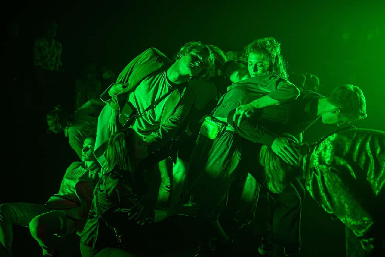 Scena spektaklu. Tłum młodych ludzi leży na sobie na kupce. Wszyscy oświetleni są na ostro zielono.