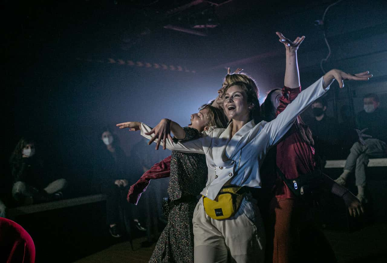 Scena spektaklu. Wielokolore zdjęcie. Młodzi ludzie stoją w jednej gurpie. Są uśmiechnięci. Część osób ma ręce wyciągnięte do góry.