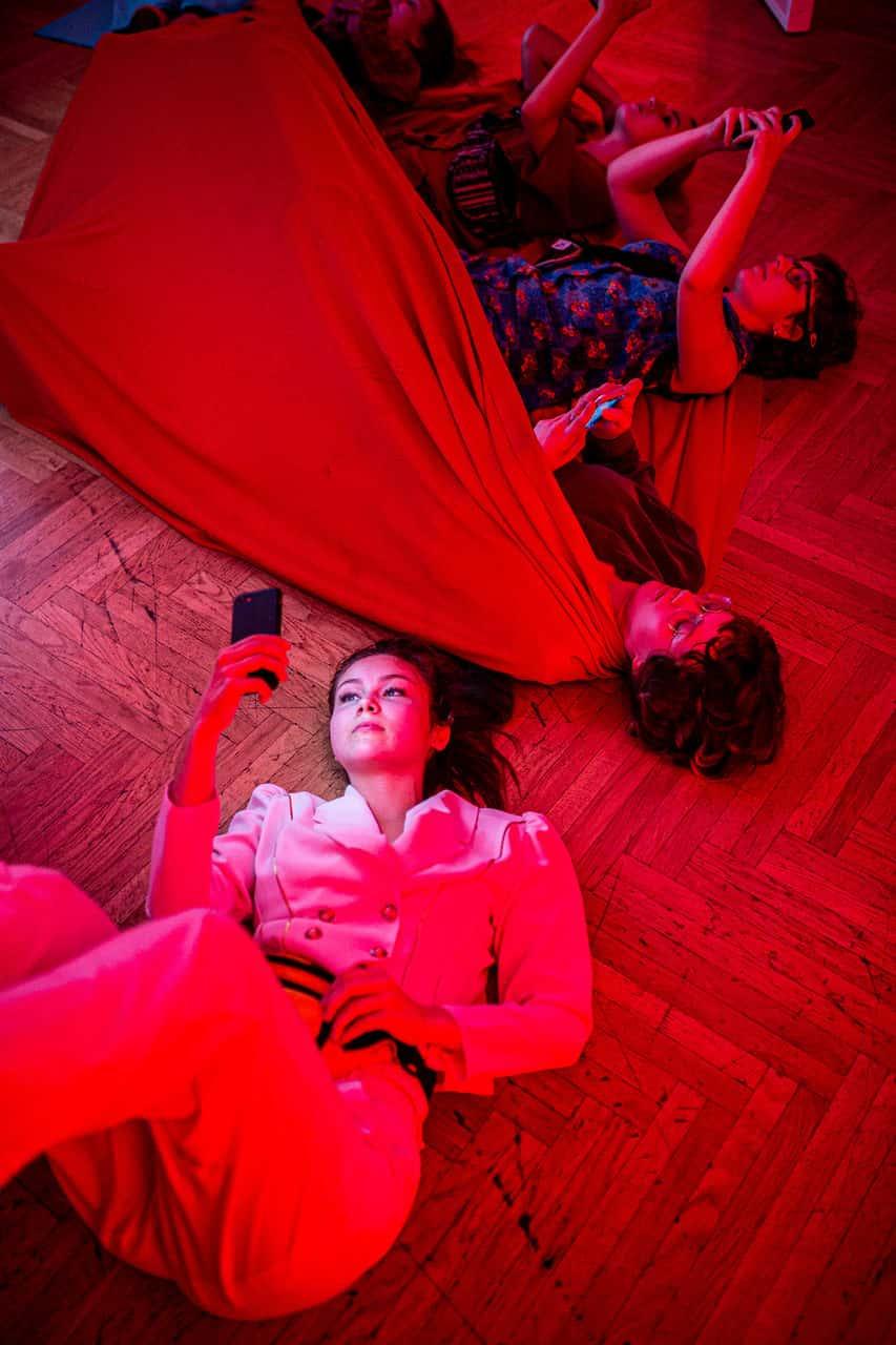 Scena spektaklu. Troje młodych ludzi leży na ziemi. Część znich przykryta jest czerwoną wielką chustą. Jedna zosób, dziewczyna, trzyma w ręku telefon komórkowy.