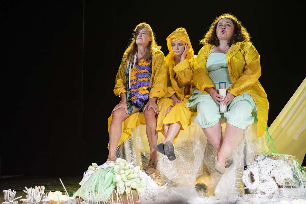 Scena spektaklu. Na podwyższeniu na scenie siedzą trzy kobiety w żółtych obszernych płaszczach przeciwdeszczowych. Wyglądają na zamyślone, dwie z nich patrząc w dal przed siebie.