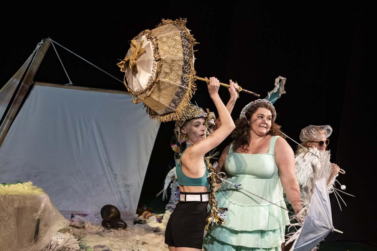 Scena spektaklu. Na scenie stoją trzy kobiety ubrane w letnie kolorowe stroje, kapelusze, okulary przeciwsłoneczne, trzymają parasolki. W tle scenografia przypominająca piaszczystą plażę i nadmorski klimat. Kobiety są uśmiechnięte, śmieją się.