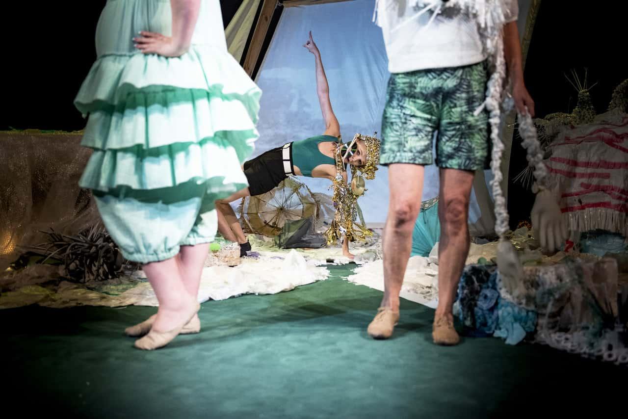 Scena spektaklu. Na pierwszym planie zbliżenie na nogi dwóch kobiet, ich sylwetki widzimy od pasa w dół, ubrane w letnie plażowe stroje. Za nimi widzimy trzecią kobietę wykonującą figurę gimnastyczną na ziemi. Ma bardzo ozdobne srebrno-złote nakrycie głowy. W tle scenografia przypominająca piaszczystą plażę i nadmorski klimat.