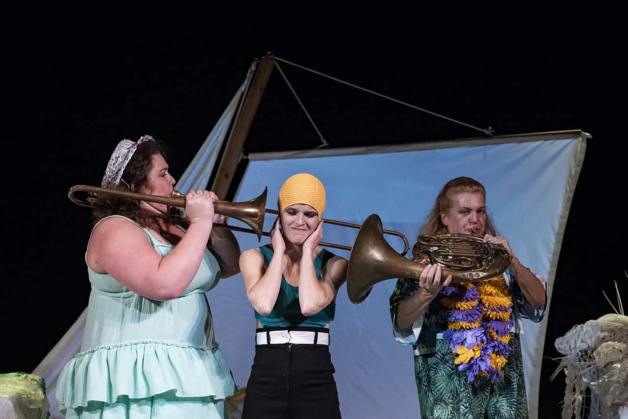 Scena spektaklu. Na scenie stoją trzy kobiety, jedna obok drugiej. Kobieta znajdująca się w środku ma na sobie żółty czepek, zakrywa dłońmi uszy, aby nie słyszeć instrumentów, które skierowały w nią dwie bohaterki obok. Jedna gra na trąbce, a druga na rogu dętym.