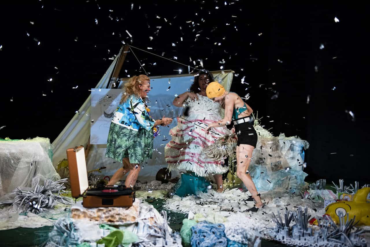 Scena ze spektaklu. Widzimy scenę, na której znajduje się dużo materiałów i rekwizytów, w powietrzu unoszą się drobinki przypominające confetti. Na środku stoją trzy roześmiane kobiety w plażowych strojach, wygląda jakby się dobrze bawiły ze sobą lub tańczyły.