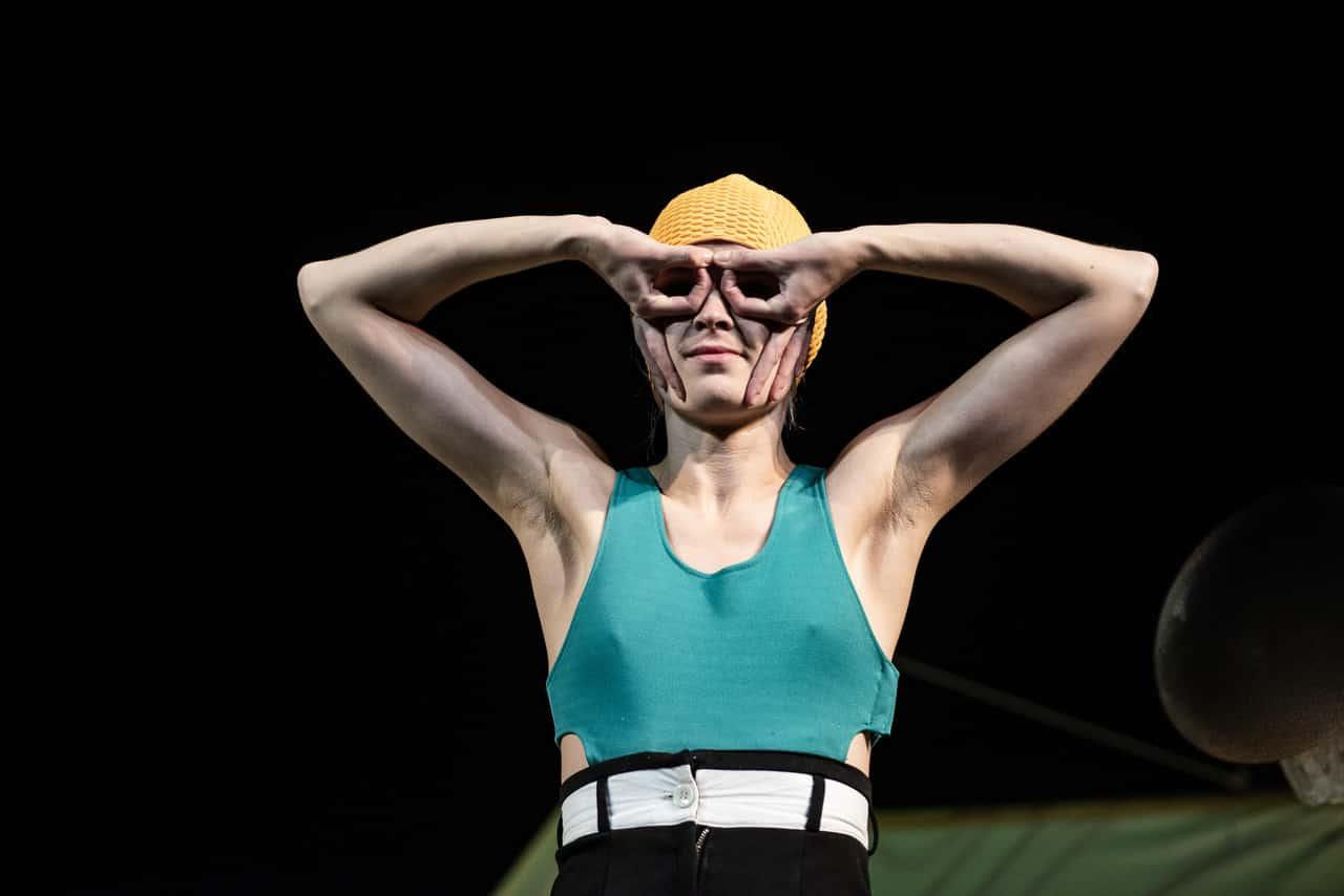 Scena ze spektaklu. WIdzimy od pasa w górę młodą kobietę w stroju kąpielowym i żółtym czepku pływackim. Twarz zakrywa sobie dłońmi, układając palce w kształt okularów lub maski.