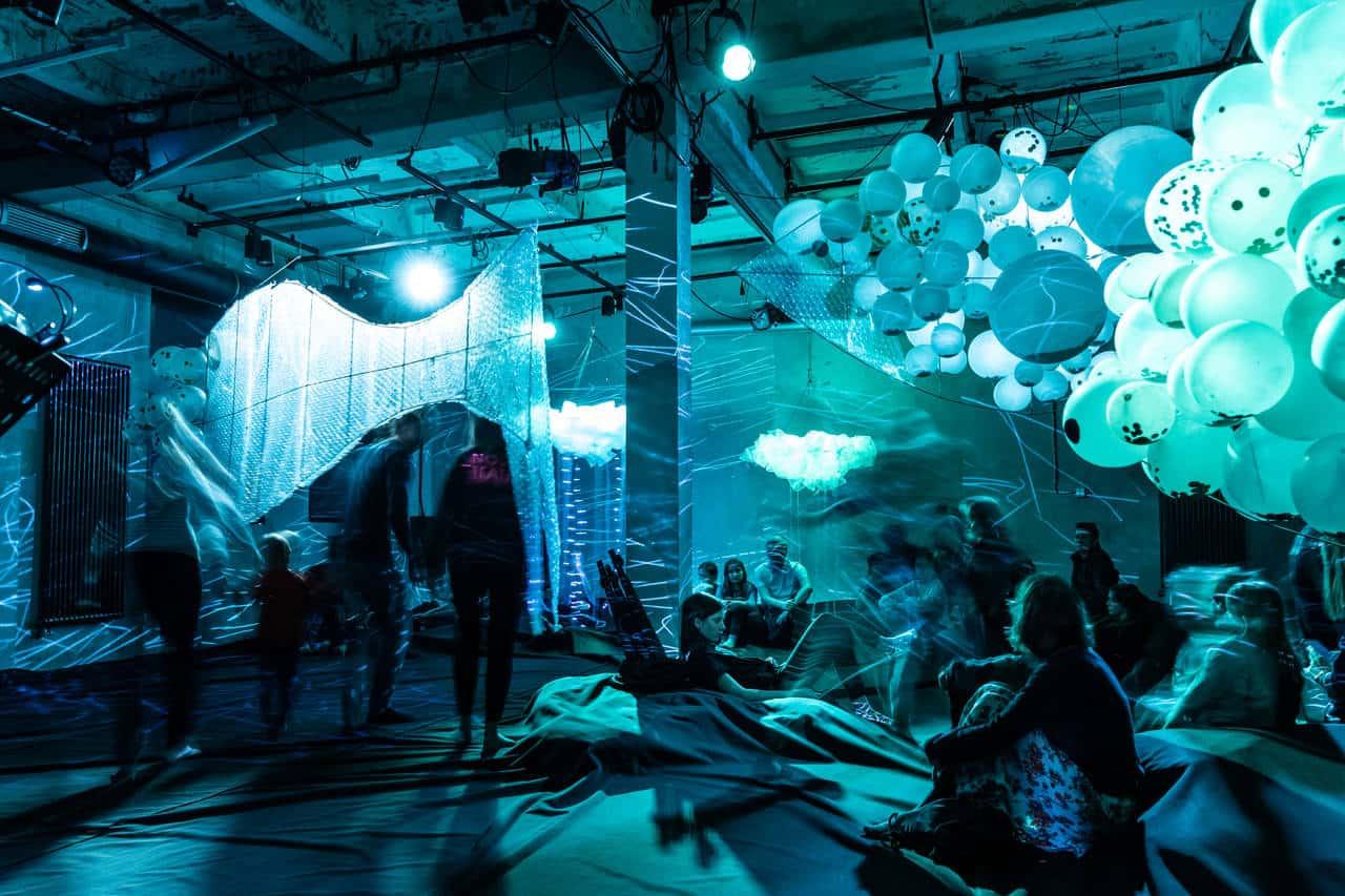 Scena z przedstawienia. Pubiczność wchodzi do sali teatralnej, która oświetlona jest cała na niebiesko-zielono. Pod sufitem zawieszone sa duże wiązki białych balonów oraz folia bąbelkowa , która tworzy rodzaj zasłony. Na podłodze rozłożona jest ciemna tkanina.