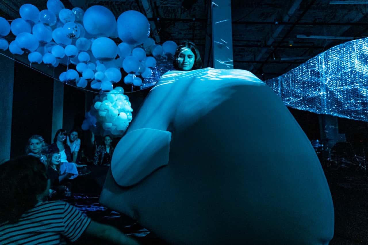 Scena spektaklu. Młoda dziewczyn siedzi na samej górze wielkiech poduszki. Poduszka ma kształt wieloryba. Cała scena oświetlona jest na niebiesko.