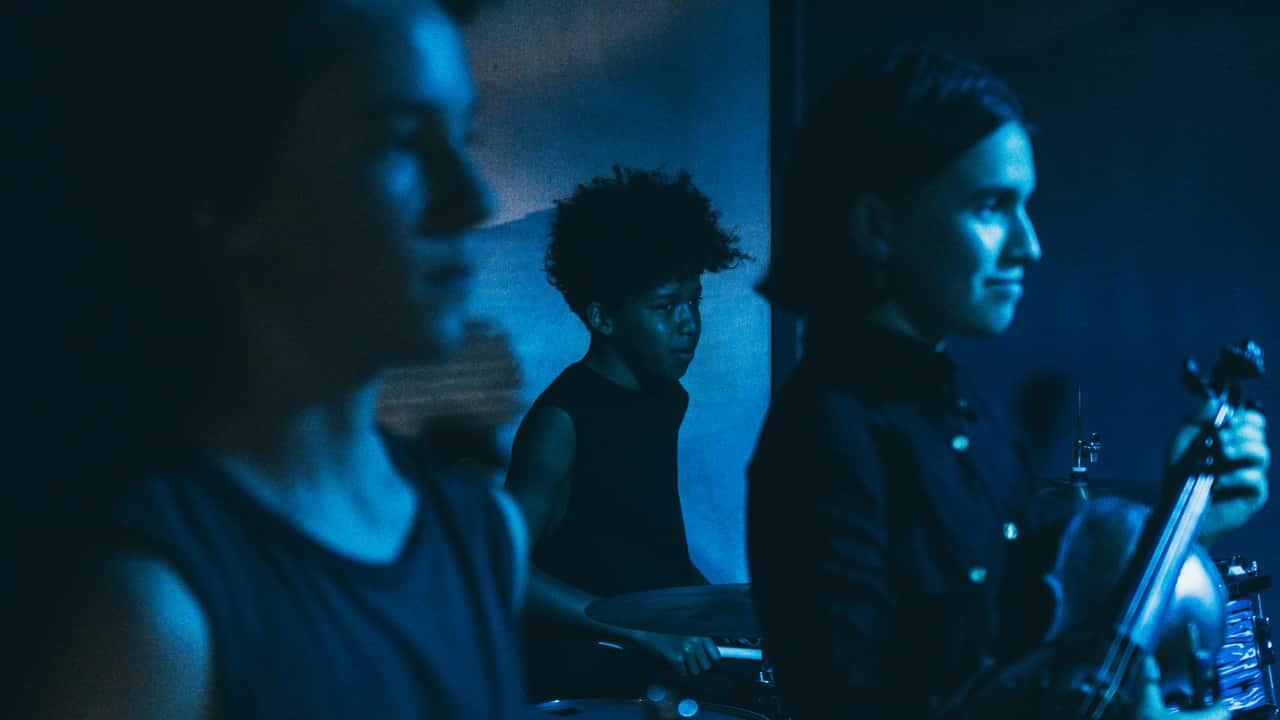 Scena spektaklu. Na zdjęciu widać trzy młode osoby, które grają w zespole akompaniującym aktorkom podczas przedstawienia. Wszyscy oświetleni są na niebiesko.