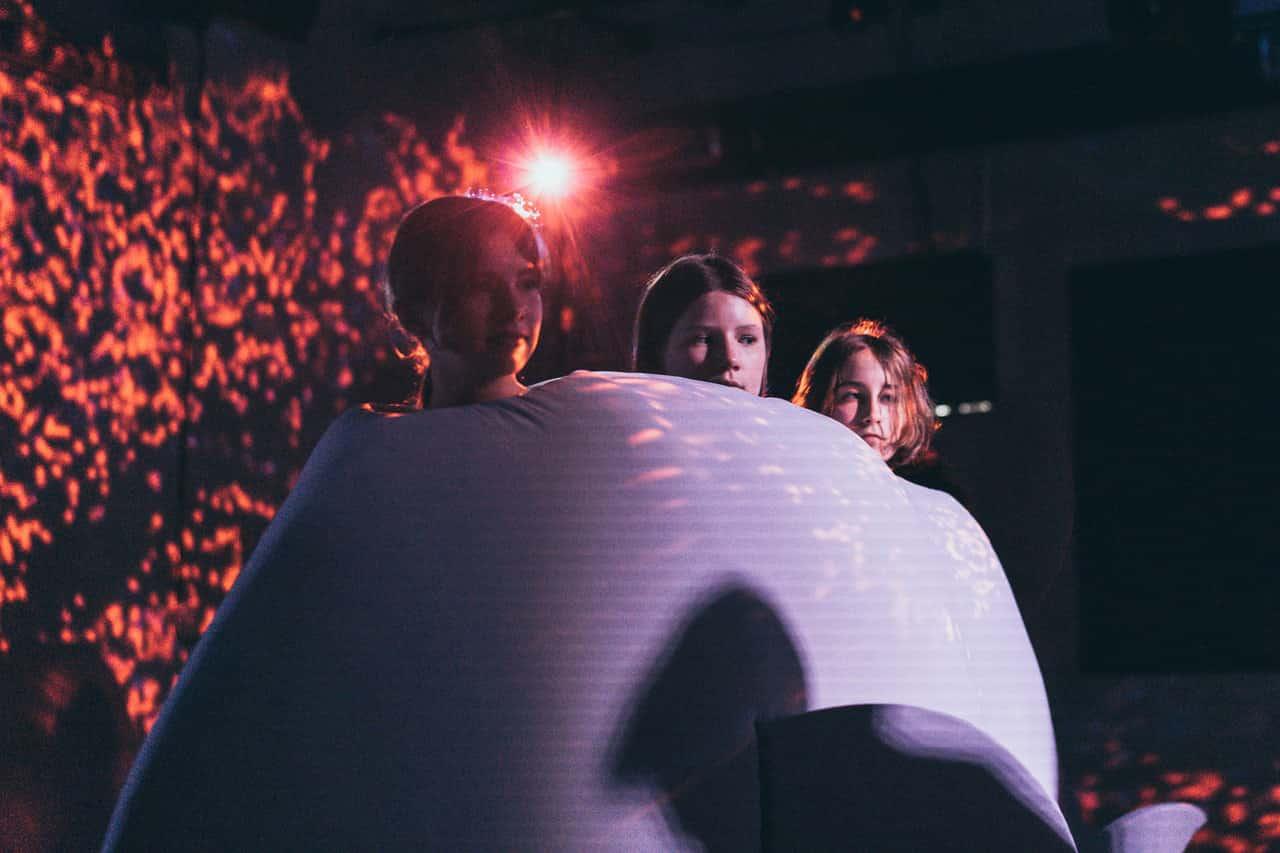 Scena zpróby do spektaklu. Na wielkiej poduszce w kształcie wieloryba siedzą trzy dziewczyny. Sylwetki postaci oświetlone są na fioletowo, twarze oświetlone są w czerwone plamki.
