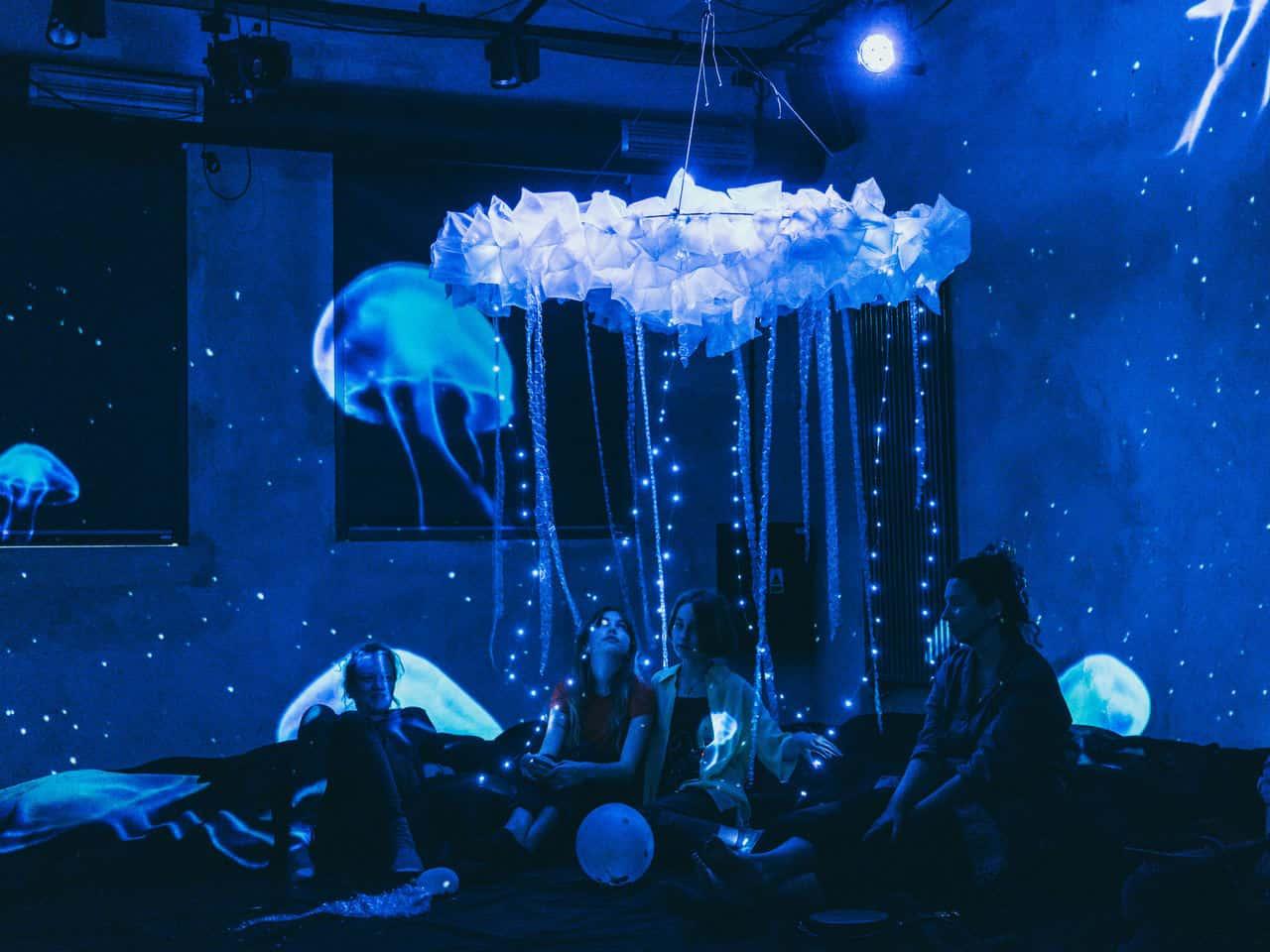 Scena zpróby do spektaklu. Na podłodze siedzą młode dziewczyny, nad nimi wisi żyrandol zbiałej krepiny, zktórego zwisają sznurki białych młych światełek choinkowych, całość wygląda jak meduza. Na ścianach widać projekcje zpływającymi meduzami.