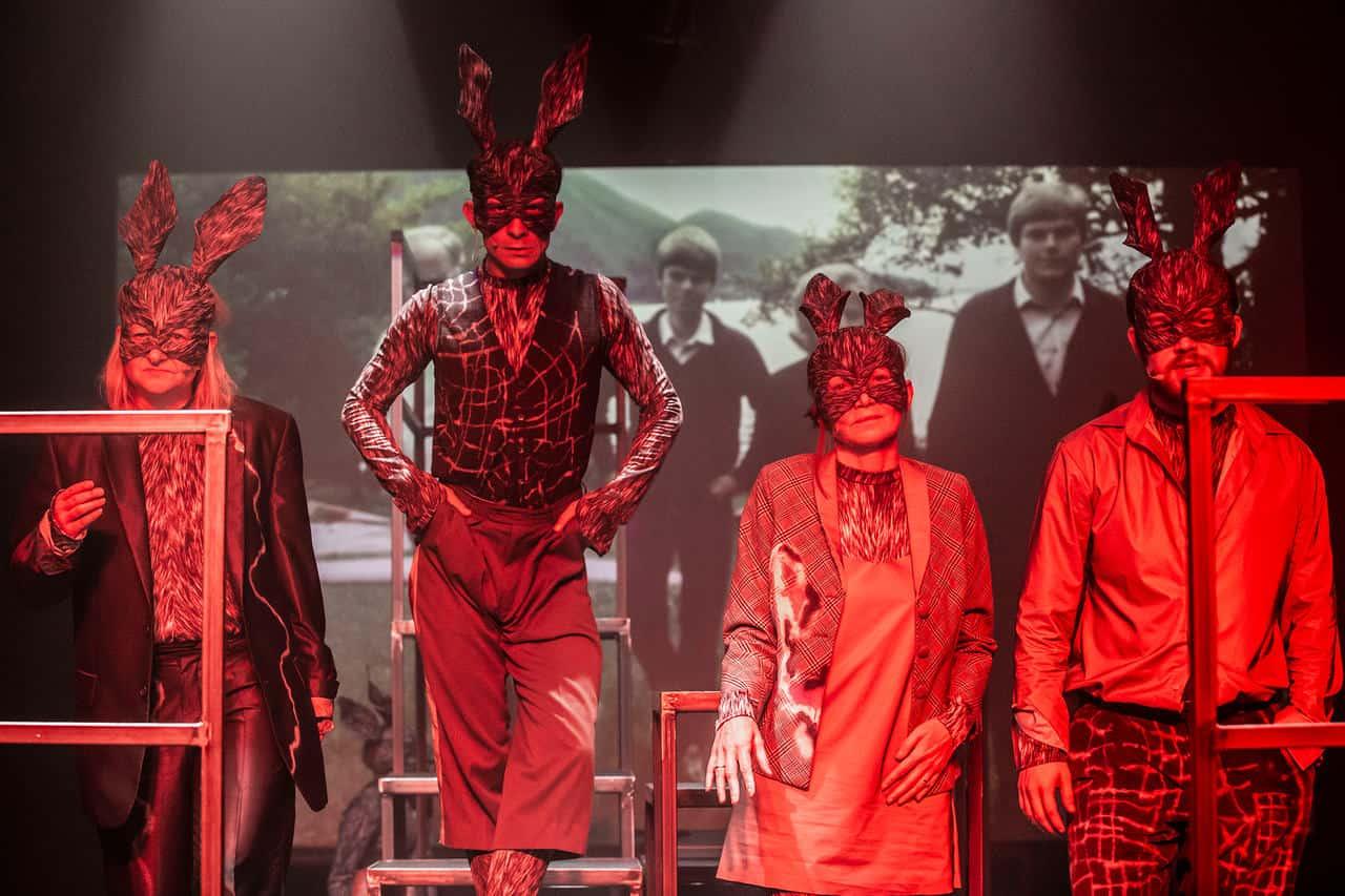Scena spektaklu. Czworo aktorów w maskách królików stoją obok siebie. Są oświetleni cali na czerwono. Za nimi na ekranie widać zdjęcie prawdopodobnie rodziny, która stoi w ten sam sposób jak aktorzy w maskách.