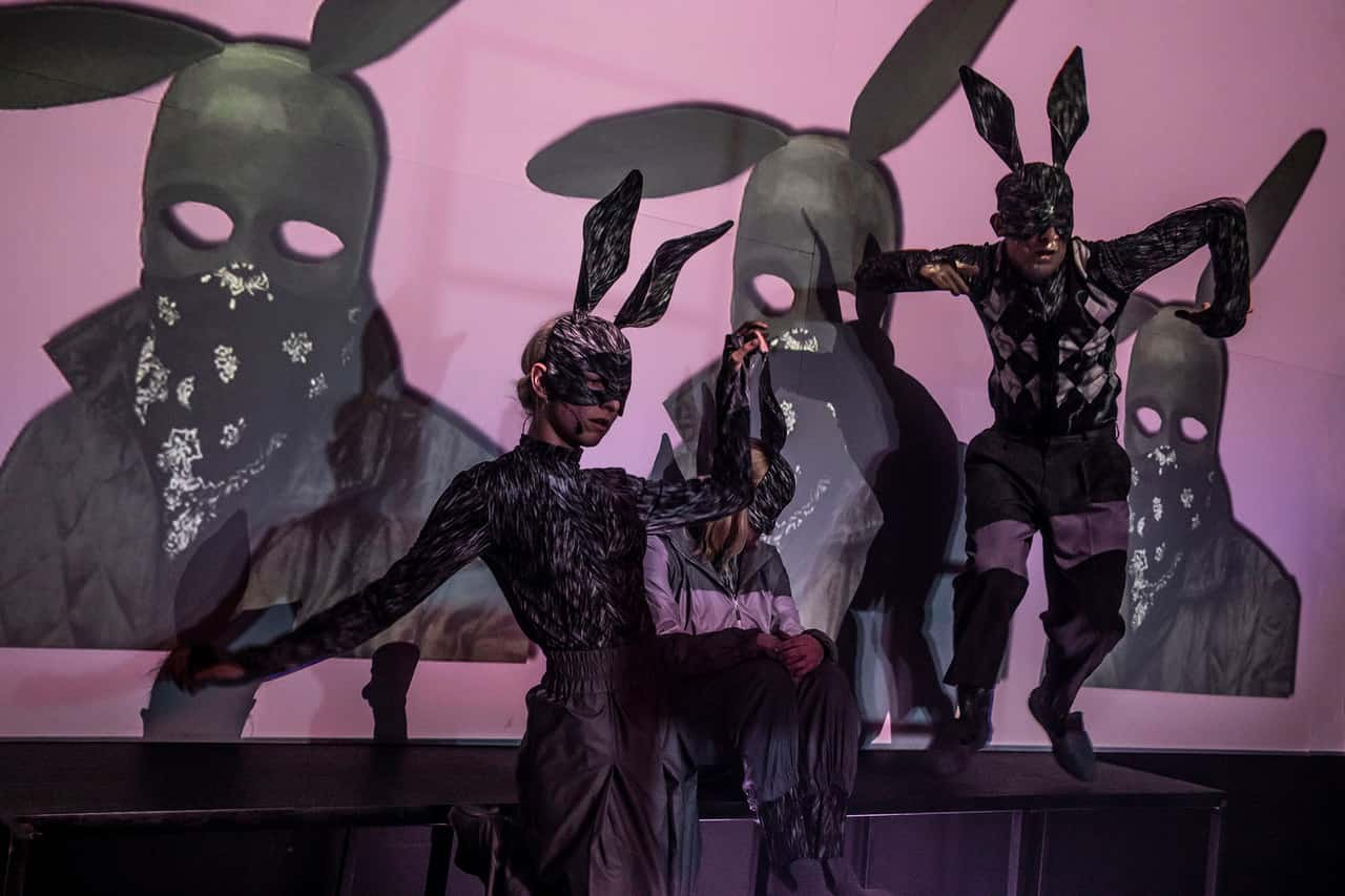 Scena spektaklu. Dwie aktorki w maskách królików, jedna stoi, druga siedzi i patrzy na ekran na którym wyswietlona jest maska królika na różowym tle. Obok trzevi kator także w masce królika skacze zpodestu.
