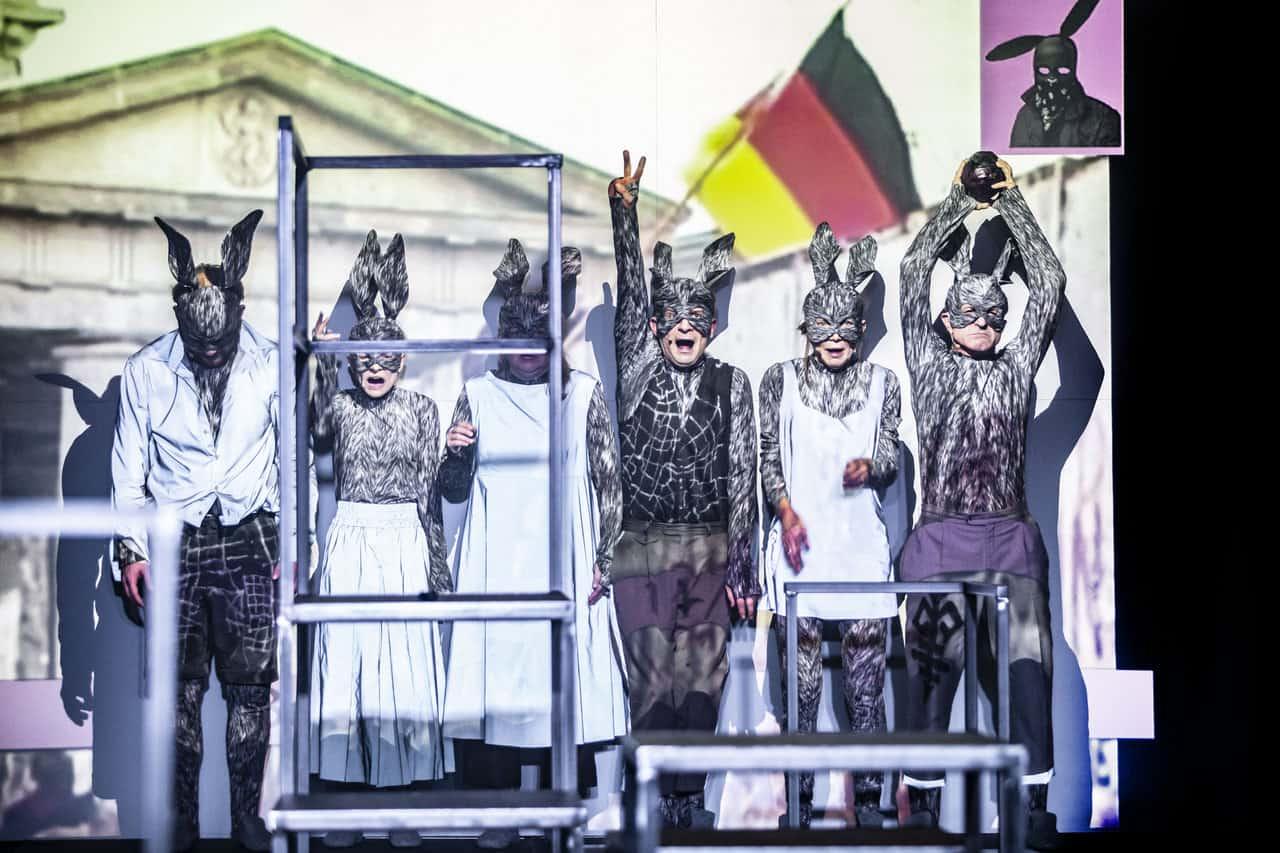 Scena spektaklu. Pod ścianą stoi sześciu aktorów, wszyscy w maskách królików. Coś krzyczą. W tle za nimi zniekształocone zdjęcie fragmentu budynku zniemiecką flagą. Jeden zaktorów ma wysoko podniesioną rękę i robi znak pokoju (Peace).