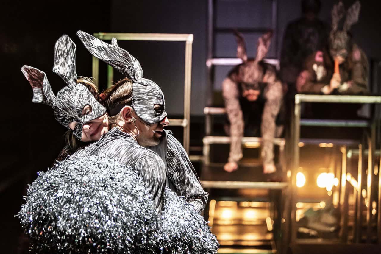 Scena spektaklu. Na pierwszym planie dwoje aktorów w maskách królików, przytula siędo siebie. W tle n dalszym planie mniej wyraźne sylwetki dwóch innych aktorów także w maskách królików leżących na rusztowaniu.