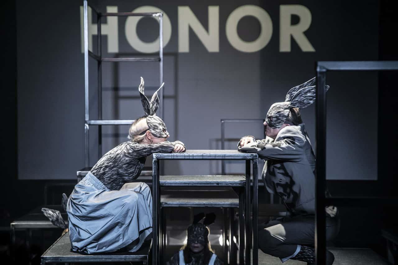 """Scena spektaklu. Dwoje aktorów, kobieta i mężczyzna, siedzi naprzeciw siebie w kuckach. Ubrani są na czarno. Oboje mają czarne maski królika. Za aktorami na ekranie swieci sięduzy napis """"HONOR""""."""