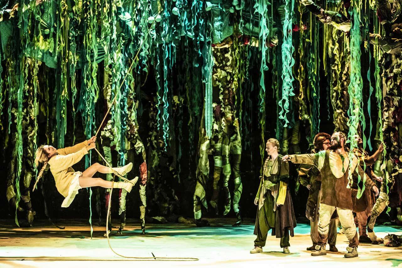 Scena spektaklu. Scena przypomina dżunglę lub bujny las ze względu na scenografię oddającą roślinność, konary drzew, zwisające gałęzie, liany. Na jednej z nich buja się kobieta obserwowana przez nieopodal stojącą grupkę ludzi w brązowych szatach.