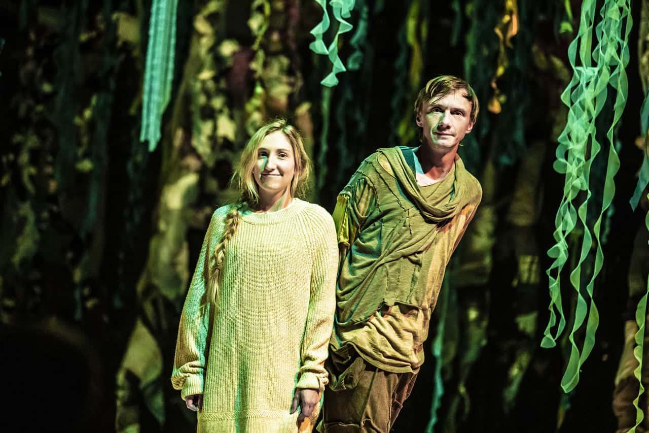 Scena spektaklu. Na scenie blisko siebie stoją dwie osoby: chłopak w brązowych podniszczonych ubraniach i uśmiechnięta dziewczyna z warkoczem i w swetrze. Za nimi znajduje się bujna roślinność przypominająca dżunglę.