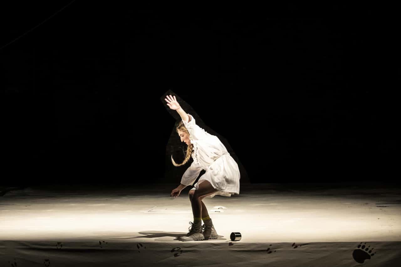 Scena spektaklu. Na środku sceny stoi dziewczyna z warkoczem. Próbuje utrzymać równowagę, chwieje się, jakby miała za chwilę upaść. Na jasnej podłodze znajdują się ciemne odciski przypominające ślady dzikich zwierząt.