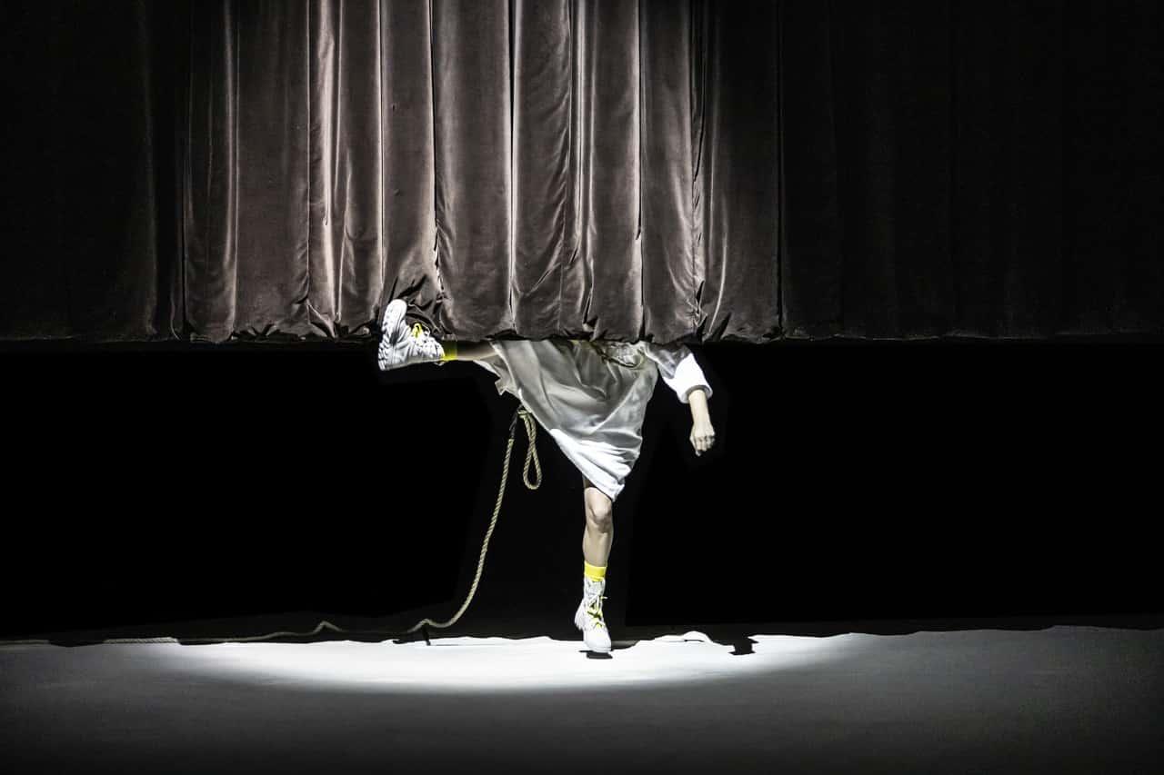 Scena spektaklu. jest ciemno, scena jest punktowo oświetlona. Na środku sceny widzimy postać, jednak górna część jej sylwetki schowana jest za opadającą kotarą z grubej błyszczącej tkaniny. Nie widzimy twarzy postaci, jedynie nogi i jedną rękę. Postać wykonuje kopnięcie, przez co jedna noga jest wysoko uniesiona.