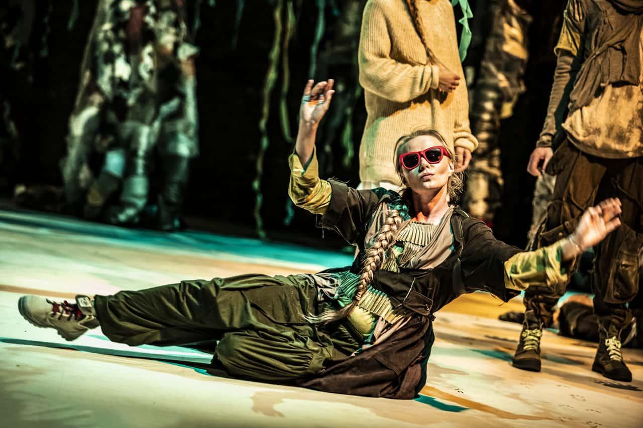 Scena spektaklu. Na podłodze siedzi młoda kobieta. Ubrana jest w ciemno zielona szaty i czerwone okulary przeciwsłoneczne. Ma uniesione lekko ręce. Za nią stoi mała grupka ludzi.