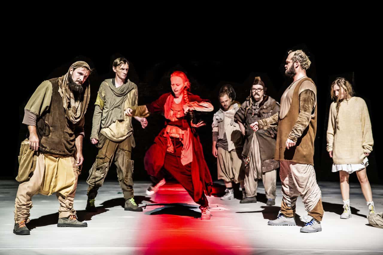 Scena spektaklu. Na środku sceny stoi mocno oświetlona grupa osób w szarych i brązowych powłóczystych szatach. Pomiędzy nimi skacze lub tańczy kobieta ubrana i pomalowana cała na czerwono.