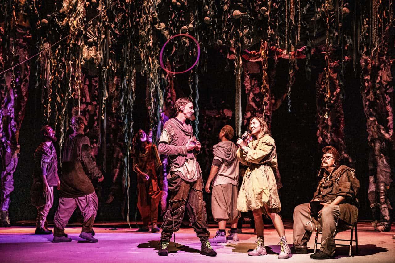 Scena spektaklu. Scena przypomina dżunglę lub bujny las ze względu na scenografię oddającą roślinność, konary drzew, zwisające gałęzie, liany. Wszystko oświetlone jest różowo fioletowym światłem. Na scenie znajduje się grupa kilku osób, są rozproszeni pomiędzy drzewami. Z przodu stoi mężczyzna i kobieta, śmieją się do siebie i rozmawiają.
