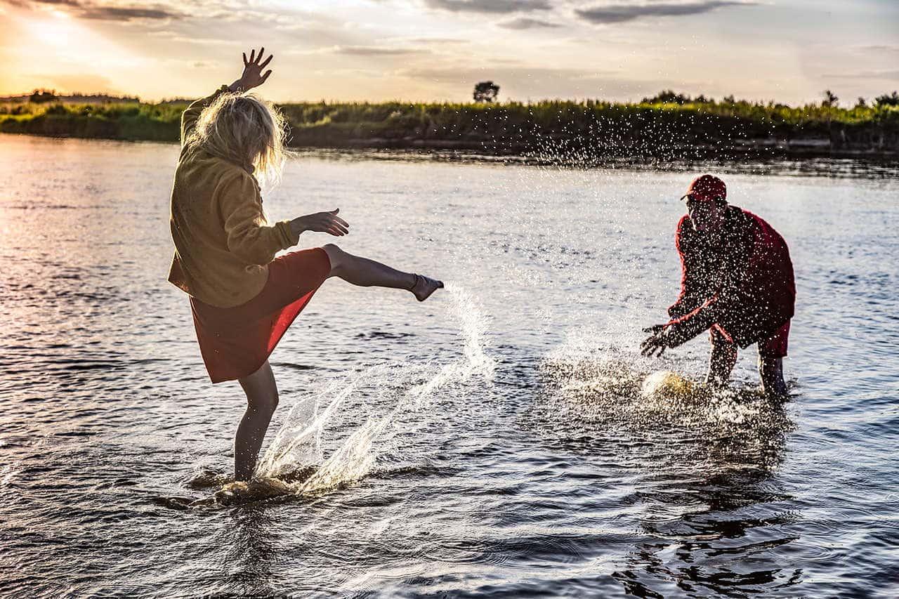 Scena w plenerze. Dwoje młodych ludzi bawi się w jeziorze, stoją w wodzie po kostki i wzajemnie się ochlapują. Kobieta ubrana jest w sukienkę i kurtkę, a mężczyzna w krótkie spodenki, kurtkę i czapkę z daszkiem. Jest wieczór, słońce już zachodzi