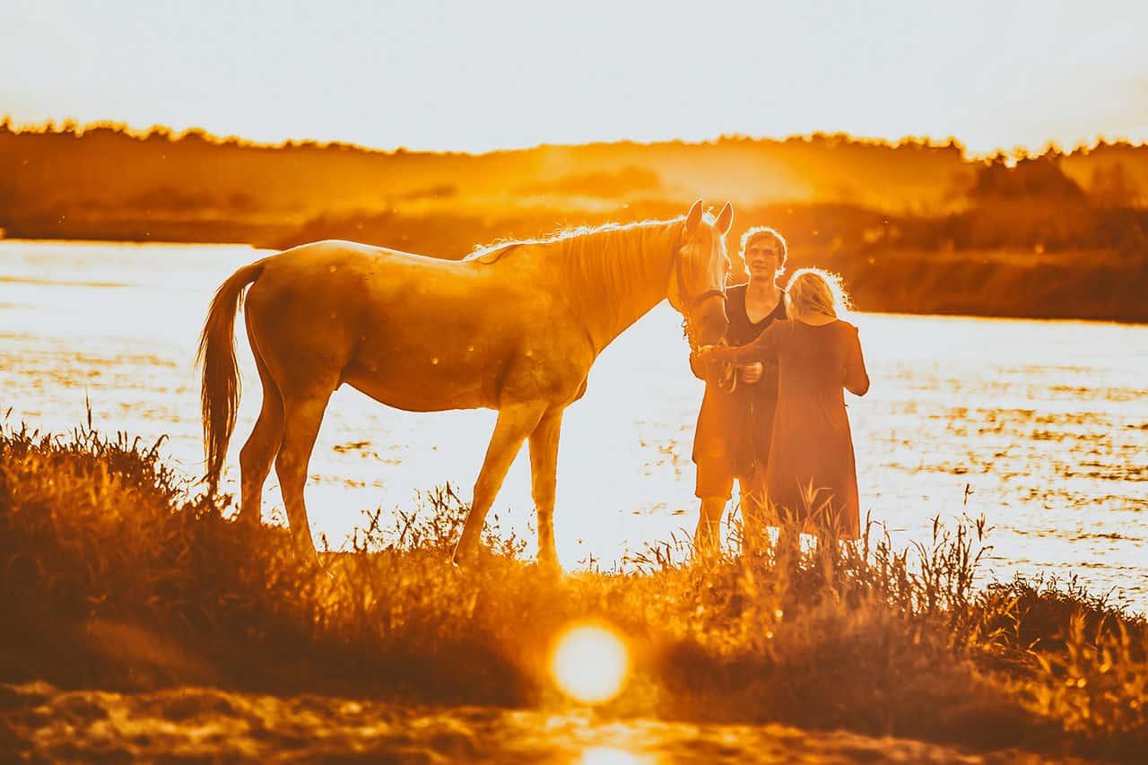 Scena w plenerze. Kobieta i mężczyzna stoją na brzegu jeziora, trzymają wspólnie za uzdę śniadego konia. Zachodzi słońce, przez co całą scenerię widzimy w ciepłych, pomarańczowych kolorach. Płynąca za nimi woda mieni się.