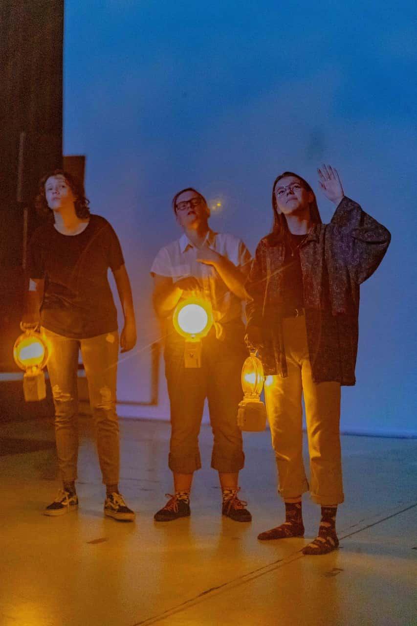 Scena spektaklu. Trzy osoby stoją na scenie. Trzymają lampy rozświetlające ciemną scenę żółtym ciepłym światłem. Głowy mają zadarte lekko do góry, wszystkie wpatrują się w ten sam punkt.