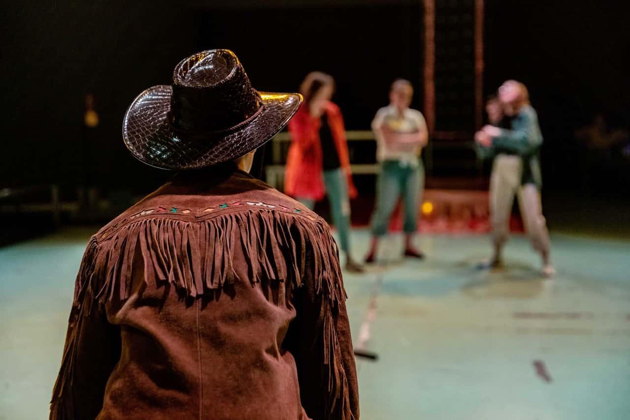 Scena spektaklu. Na pierwszym planie widzimy postać ubraną w kowbojski kapelusz z rondem i brązową kurtkę z frędzlami na ramionach i rękawach. Nie widzimy jego lub jej twarzy, ale pewnie spogląda na trzy kobiety stojące dalej na scenie.