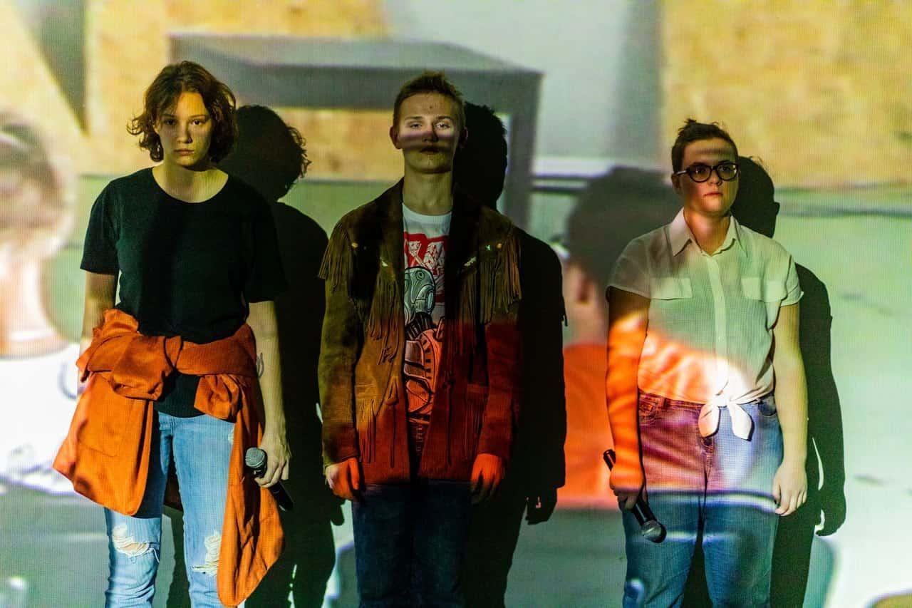 Scena spektaklu. Trzy postaci stoją obok siebie, za plecami mają jasne tło lub ścianę. Są poważni, patrzą się spokojnie przed siebie, nie ma interakcji między nimi. Na ich sylwetki pada projekcja filmowa lub zdjęciowa, rzucając kolorowy obraz na nich i na jasne tło za nimi.