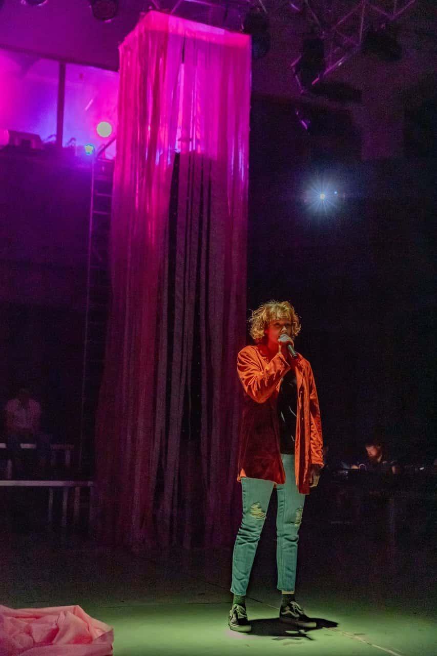 Scena spektaklu. Na scenie Stoi kobieta w czerwonej kurtce, jest sama, w ręce trzyma mikrofon, do którego mówi lub śpiewa. Jej postać jest oświetlona, a za nią widać instalację złożoną z długich pasów różowego materiału.