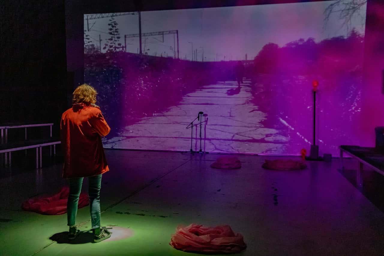 Scena spektaklu. Na scenie plecami do widzów stoi kobieta. Sala jest zaciemniona, przed nią na ścianę puszczono projekcję filmową. Bohaterka obserwuje niewyraźny obraz - pustą drogę, przez którą biegnie postać. Pod ścianą z projekcją stoi mikrofon na statywie.
