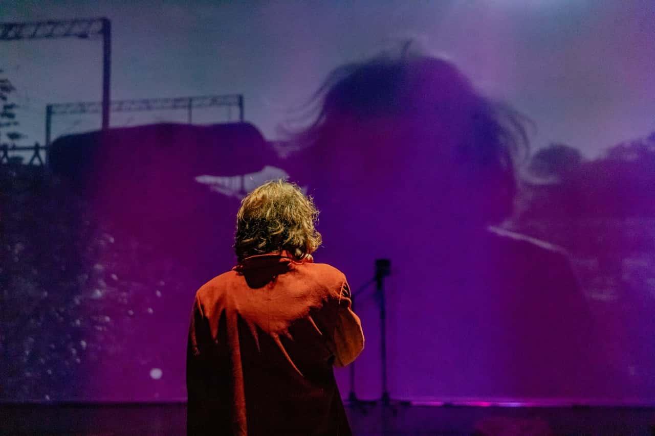 Scena spektaklu. Na scenie plecami do widzów stoi kobieta. Sala jest zaciemniona, przed nią na ścianę puszczono projekcję filmową. Bohaterka obserwuje niewyraźny obraz i zarys ludzkiej sylwetki.