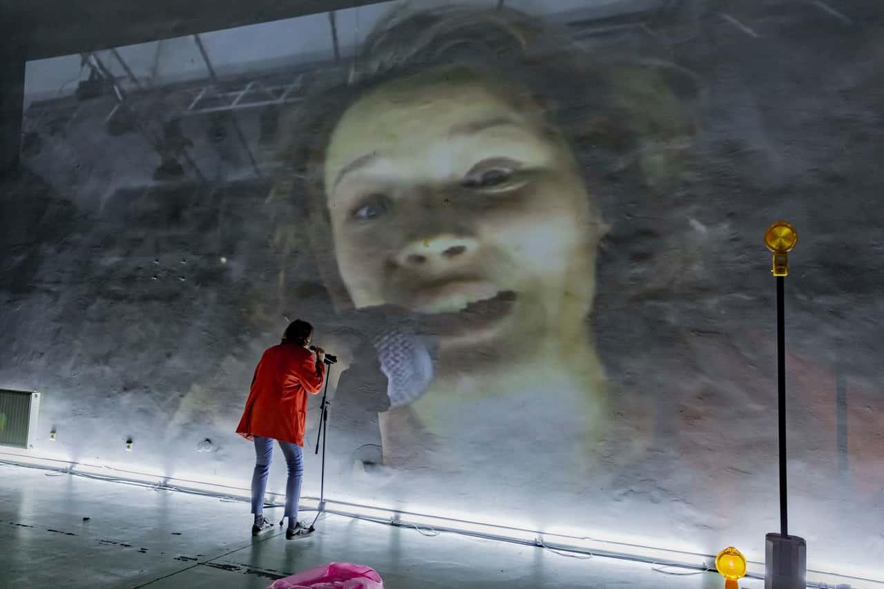 Scena spektaklu. Na ogromną ścianę puszczono projekcję filmową, na której widać kobiecą twarz. Tuż pod ścianą, przodem do projekcji stoi postać z mikrofonem na statywie.