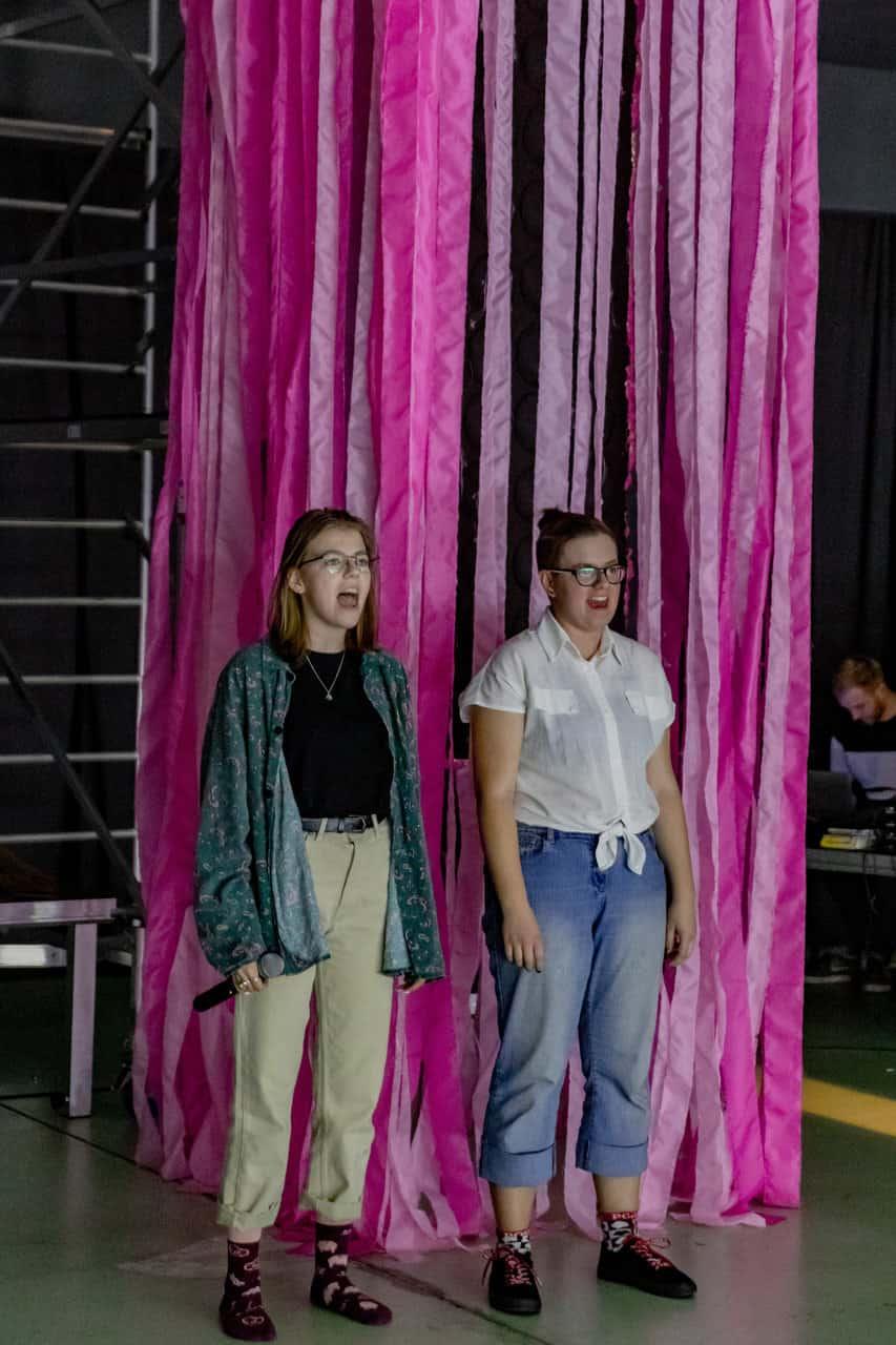 Scena spektaklu. Dwie młode dziewczyny stoją obok siebie. Mają otwarte usta jakby śpiewały lub krzyczały. Jedna z nich ma mikrofon w dłoni. Za nimi znajduje się instalacja złożona z długich pasów różowego materiału.